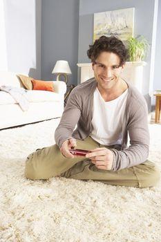 Young Man Looking At Photograph On Digital Camera At Home