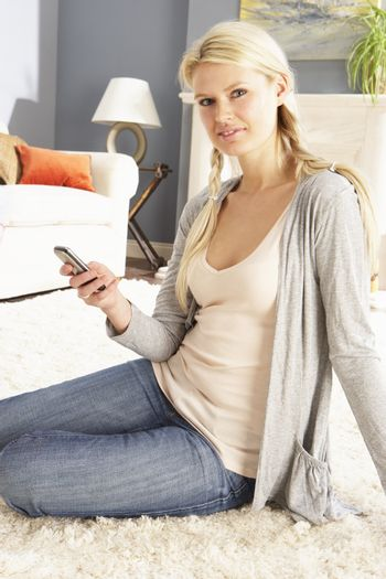 Woman Using Mobile Phone Relaxing Sitting On Rug At Home