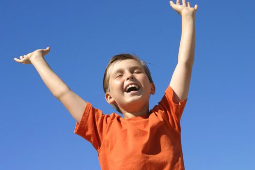 A boy shows joy, success praise or triumph