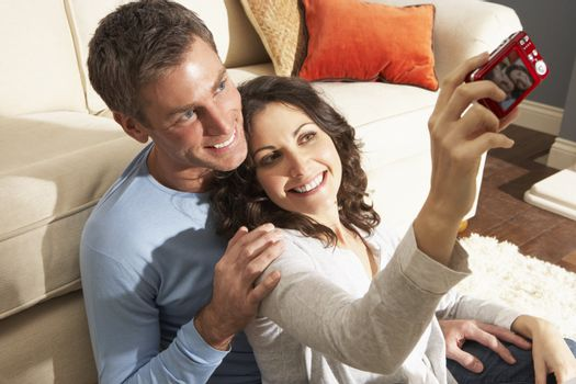 Couple Taking Photograph On Digital Camera At Home