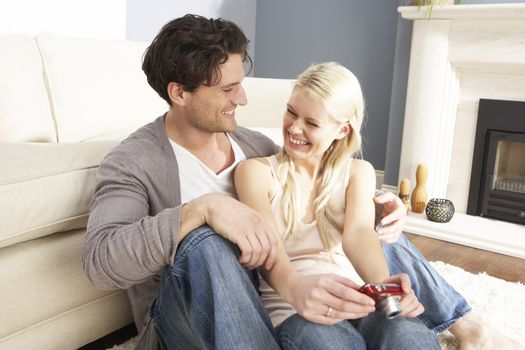 Couple Looking At Pictures On Digital Camera At Home
