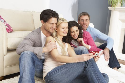 Group Of  Friends Looking At Pictures On Digital Camera At Home
