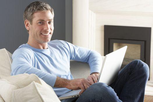 Man Using Laptop Relaxing Sitting On Sofa At Home