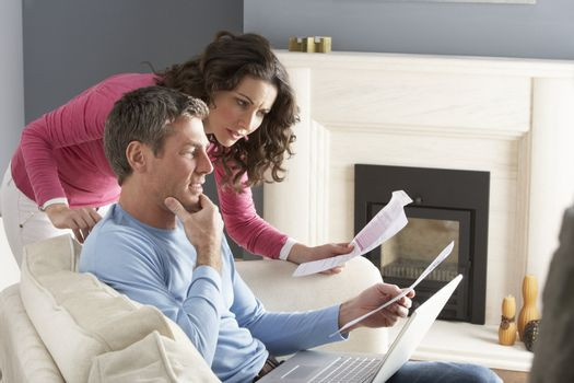 Couple Using Laptop And Discussing Household Bills Sitting On So