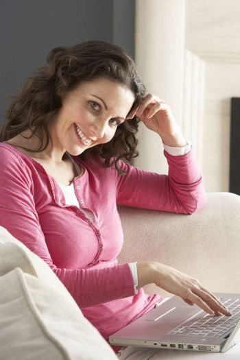Woman Using Laptop Relaxing Sitting On Sofa At Home