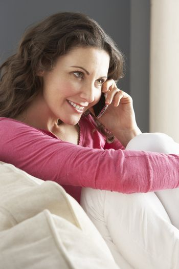 Woman Relaxing Sitting On Sofa At Home Talking On Phone