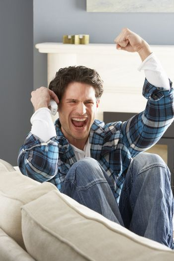 Excited Man Sitting On Sofa At Home Talking On Phone