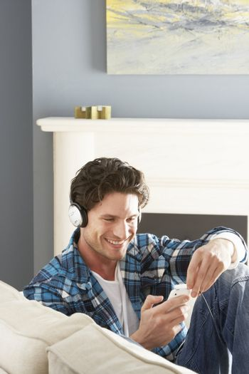 Man Listening To MP3 Player On Headphones Relaxing Sitting On Sofa At Home