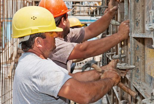 Construction workers positioning cement formwork frames