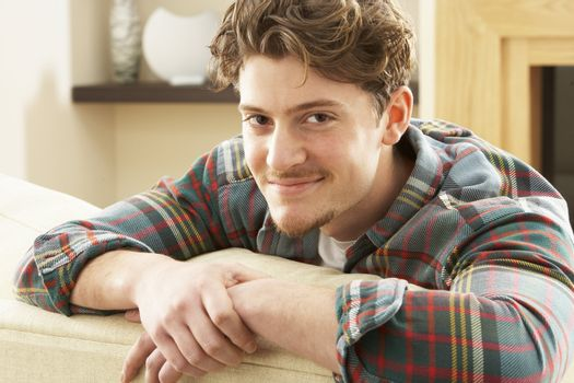 Man Relaxing On Sofa At Home