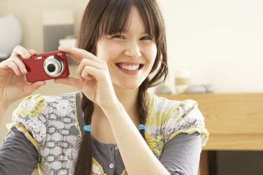 Young Woman Taking Photograph On Digital Camera At Home