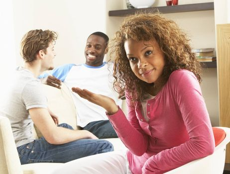 Two Male Friends Chatting Together With Bored Looking Female Partner At Home