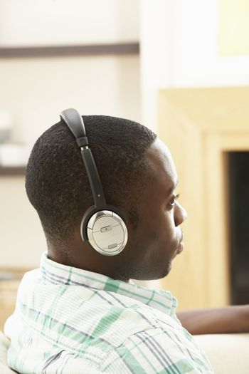 Young Man Relaxing Sitting On Sofa Listening to Music At Home On Headphones