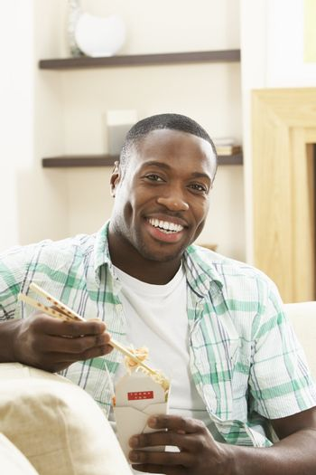 Young Man Relaxing Sitting On Sofa At Eating Chinese Meal At Home