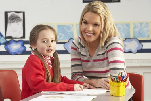 Female Primary School Pupil And Teacher Working At Desk In Classroom