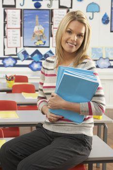 Portrait Of Female Teacher Sitting At Desk In Classroom