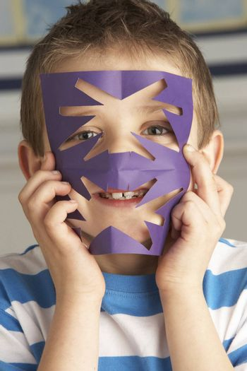 Male Primary School Pupil Cutting Out Paper Shapes In Craft Lesson