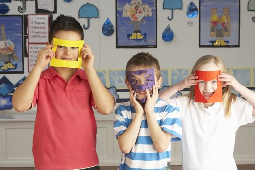 Group Of Primary School Children Cutting Out Paper Shapes In Craft Lesson