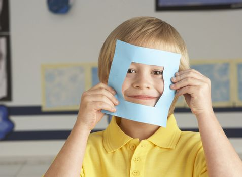 Male Primary School Cutting Out Paper Shapes In Craft Lesson