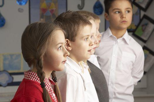 Portrait Of Group Of Primary Schoolchildren Standing In Classroom