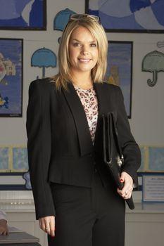 Portrait Of Female Primary School Teacher Standing In Classroom