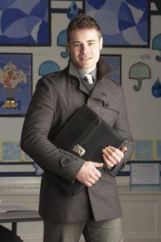 Portrait Of Male Primary School Teacher Standing In Classroom
