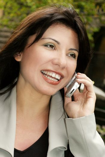 Happy brunette using a mobile cell phone