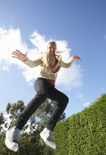Young Woman Jumping On Trampoline Caught In Mid Air