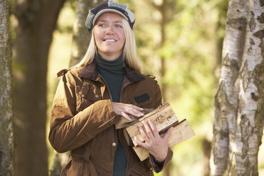 Woman Outdoors In Autumn Woodland Gathering Logs