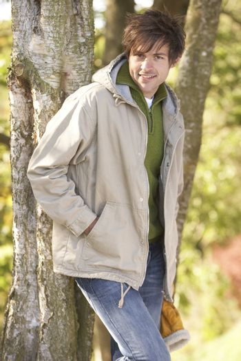 Young Man Outdoors Walking In Autumn Woodland