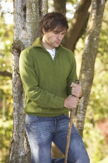 Young Man Outdoors Walking In Autumn Woodland Holding Walking St