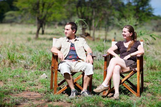 Safari vacation. Young couple in safari clothes sitting outdoor at lodge in central Serengeti, Tanzania