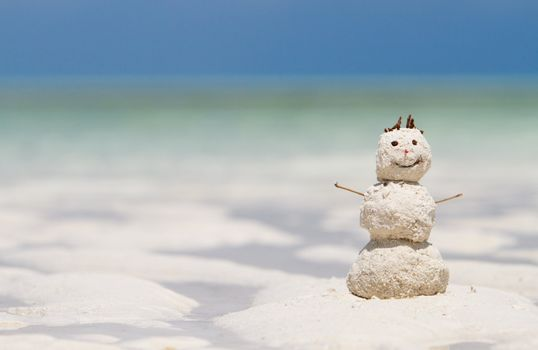 Winter vacation. Snowman made from white tropical sand on exotic beach with ocean on background.