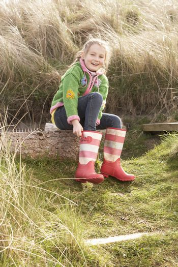 Young Girl Putting On Wellington Boots
