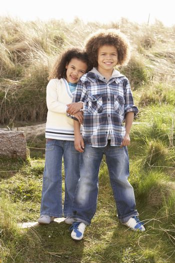 Boy And Girl Playing In Field Together