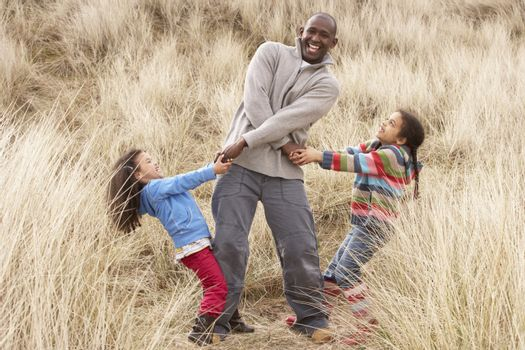 Father And Daughters Having Fun In Sand Dunes