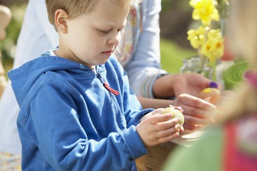 Mother And Children Decorating Easter Eggs On Table Outdoors