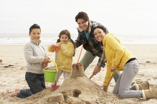 Family Building Sandcastle On Winter Beach