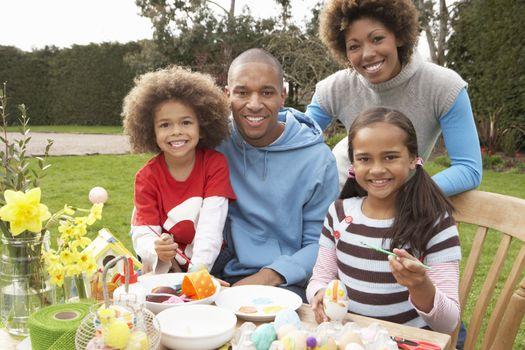 Family Painting Easter Eggs In Gardens