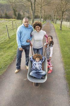 Family Having Ride In Wheelbarrow In Countryside