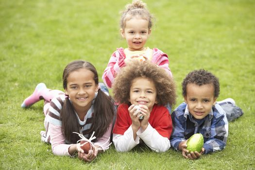 Group Of Children Laying On Grass With Easter Eggs