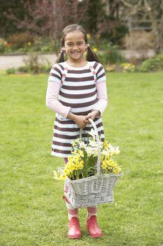 Girl Holding Basket Of Daffodils In Garden
