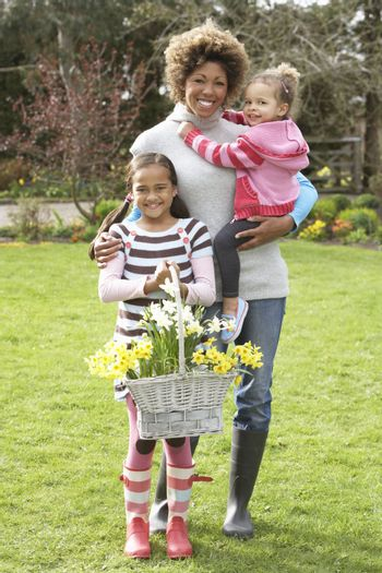 Mother And Children Holding Basket Of Daffodils In Garden