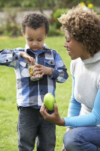 Mother Helping Son To Unwrap Chocolate Easter Egg