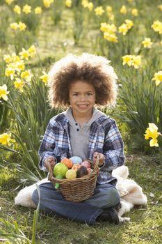 Boy On Easter Egg Hunt In Daffodil Field