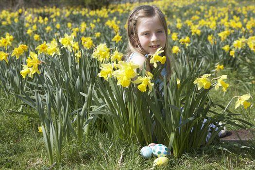 Girl On Easter Egg Hunt In Daffodil Field
