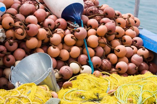 Nylon yellow  fishing net, metal bucket, buoy close-up on the boat desk