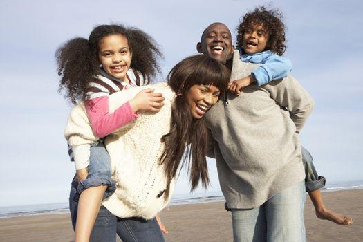 Family Having Fun On Winter Beach