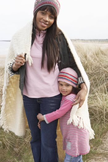 Mother And Daughter Wrapped In Blanket Amongst Dunes On Winter Beach