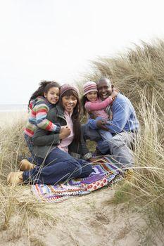 Family Sitting On Blanket In Dunes On Winter Beach
